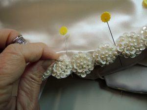 mani che cuciono un abito da sposa