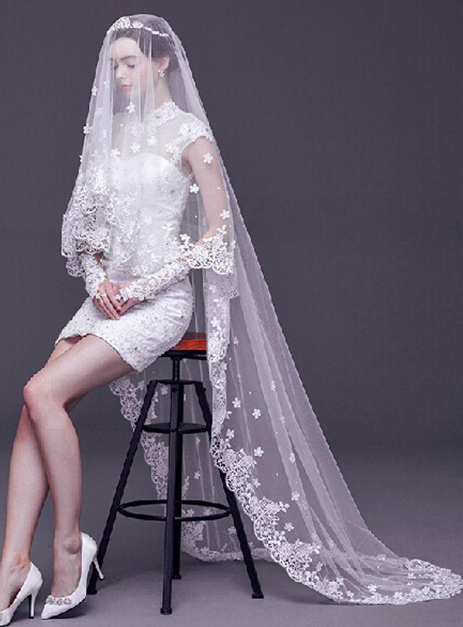 velo da sposa lungo indossato su un abito corto